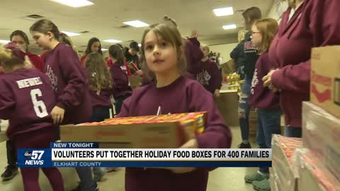 Volunteers fill boxes with food to feed 400 families in Elkhart...
